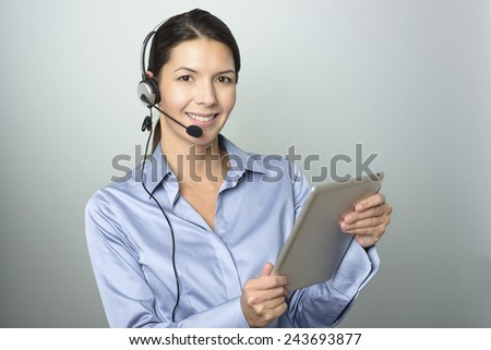 Portrait of Smiling Young Customer Representative Woman with Headset Holding Tablet Computer While Looking at the Camera. Isolated on Gray Background. - stock photo
