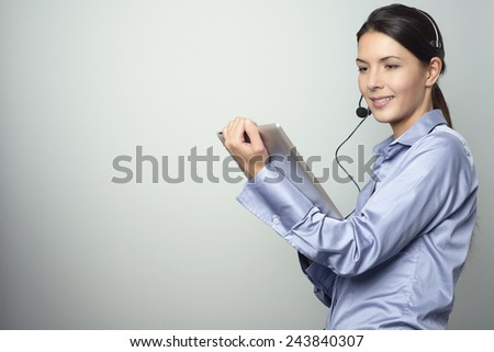 Portrait of Smiling Young Customer Representative Woman with Headset working with her Tablet Computer, Isolated on Gray Background. - stock photo
