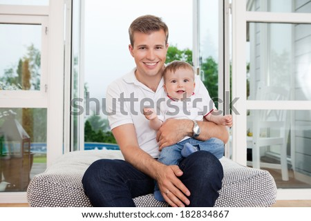 Portrait of smiling young father with child sitting on couch - stock photo