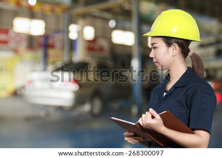 Portrait of smiling young female mechanic inspecting on a car in auto repair shop - stock photo
