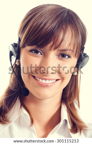 Portrait of smiling young female support phone operator or call center worker in headset - stock photo