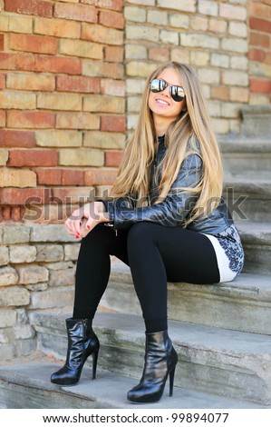 Portrait of smiling young girl sitting on the stairs in sunglasses - stock photo