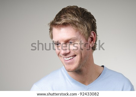 portrait of smiling young man in blue sweater - stock photo