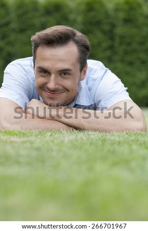 Portrait of smiling young man lying on grass in park - stock photo