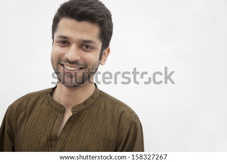 Portrait of smiling young man wearing traditional clothing from Pakistan - stock photo