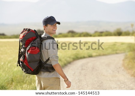 Portrait of smiling young man with backpack walking on country road - stock photo