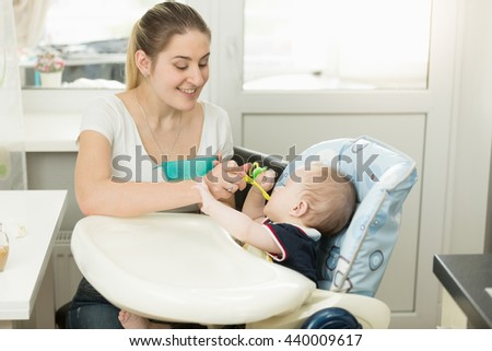 Portrait of smiling young mother feeding her baby in highchair - stock photo