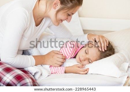 Portrait of smiling young mother holding hand on sleeping daughters head - stock photo