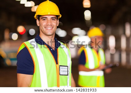 portrait of smiling young warehouse worker indoors - stock photo
