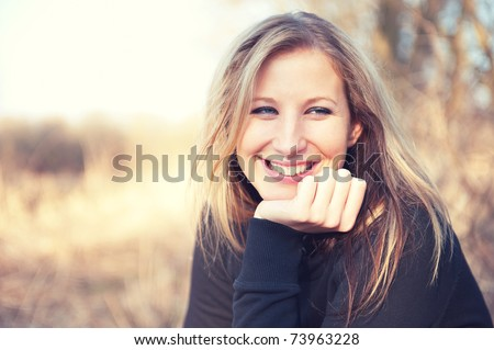 Portrait of smiling young woman enjoying at the park - Outdoor. Warm colors - stock photo