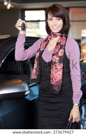 Portrait of smiling young woman holding car key - stock photo