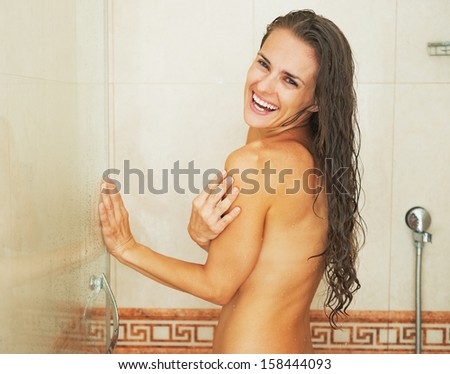 Portrait of smiling young woman in shower - stock photo