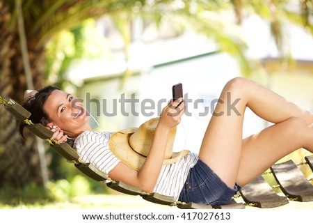 Portrait of smiling young woman lying on hammock listening to music on mobile phone - stock photo
