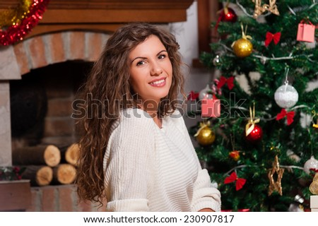 Portrait of smiling young woman near christmas tree over living room. - stock photo