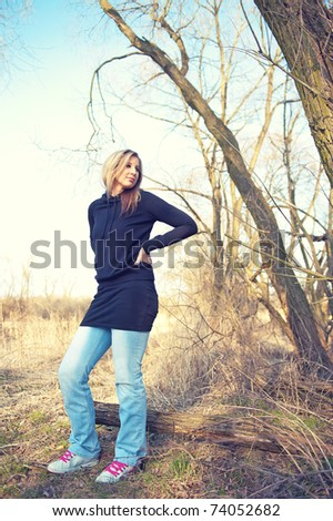 Portrait of smiling young woman posing at the park - stock photo