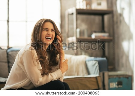 Portrait of smiling young woman talking cell phone in loft apartment - stock photo