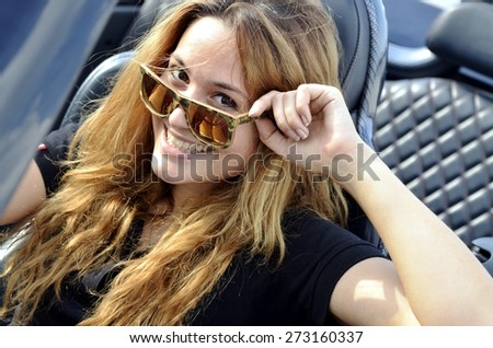 Portrait of smiling young woman wearing sunglasses in the sportive cabriolet.  - stock photo