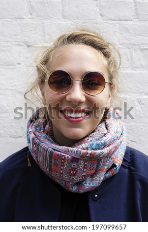Portrait of smiling young woman wearing sunglasses, United Kingdom - stock photo