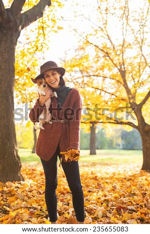 Portrait of smiling young woman with dog outdoors in autumn - stock photo