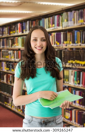 Portrait of smiling young woman with file against close up of a bookshelf - stock photo
