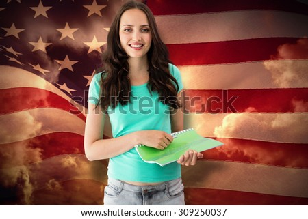 Portrait of smiling young woman with file against composite image of digitally generated united states national flag - stock photo