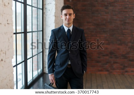 Portrait of smilling businessmen in elegant clothes near window standing modern office - stock photo