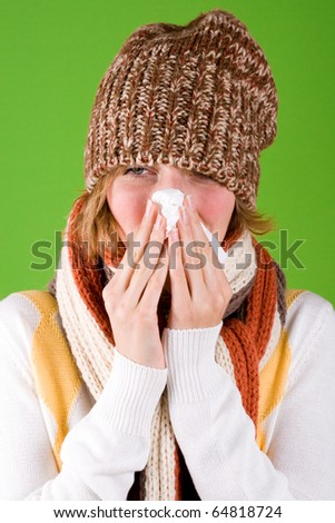 portrait of sneezing woman with handkerchief on green background - stock photo