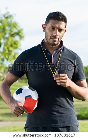 Portrait of soccer coach standing outdoors - stock photo