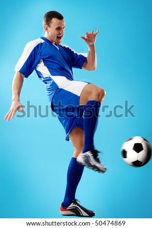 Portrait of soccer player hitting the ball - stock photo
