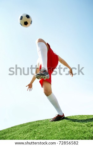 Portrait of soccer player kicking ball by knee on football field - stock photo