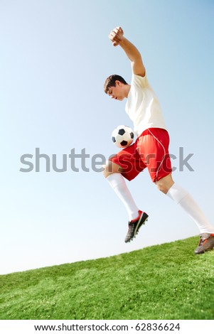 Portrait of soccer player with ball over leg playing on football field - stock photo