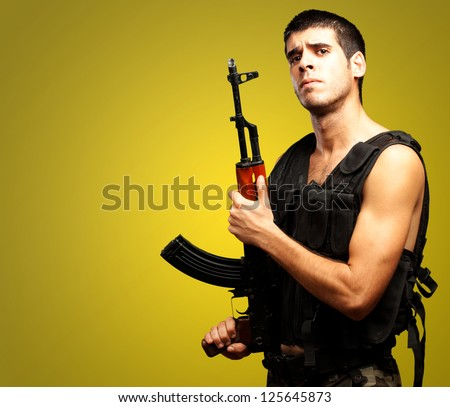 Portrait Of Soldier Holding Gun against a yellow background - stock photo