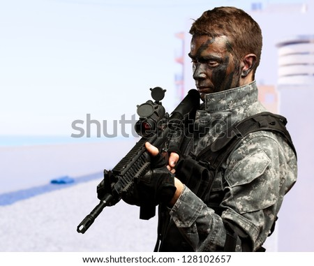 Portrait Of Soldier Holding Gun at a beach - stock photo