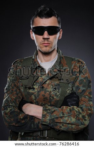 portrait of soldier in camouflage and ammunition . studio shot - stock photo