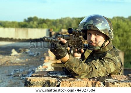 Portrait of soldier in camouflage with machine gun - stock photo
