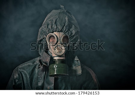 Portrait of soldier in chemical protection armor and gas mask with smoke in background - stock photo