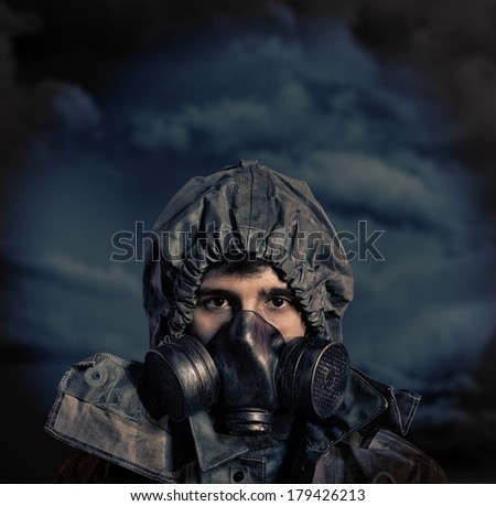 Portrait of soldier in chemical protection armor and gas mask with stormy sky in background - stock photo