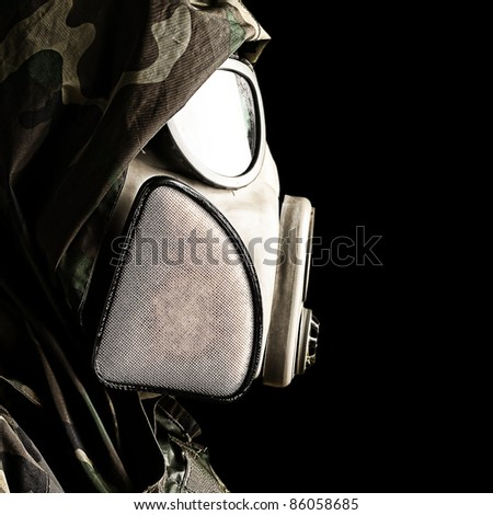 portrait of soldier with gas mask against a black background - stock photo