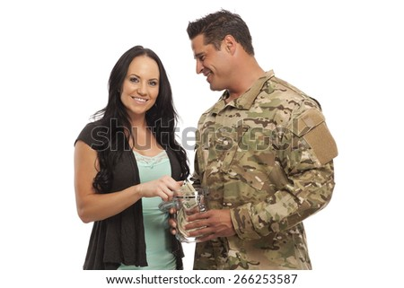 Portrait of soldier with his wife collecting money in jar against white background - stock photo