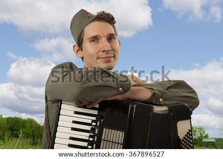 Portrait of Soviet soldier in uniform of World War II with accordion on the blue sky background  - stock photo