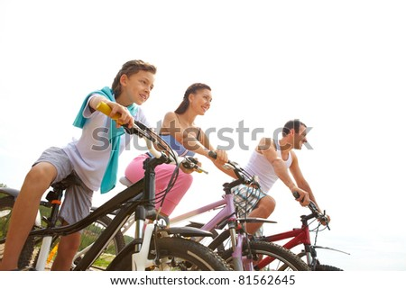 Portrait of sportive family of three on bikes - stock photo