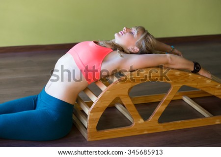 Portrait of sporty beautiful young blond woman in sportswear working out indoors, doing exercise for spine and shoulders flexibility and correct posture on Viparita Dandasana backbend bench - stock photo