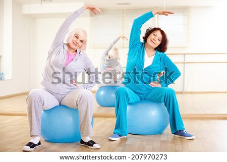 Portrait of sporty females doing physical exercise on balls in sport gym  - stock photo