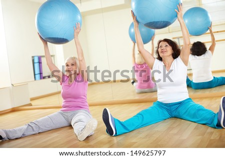 Portrait of sporty females doing physical exercise with fitness balls in sport gym  - stock photo