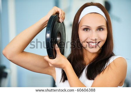 portrait of sporty girl posing with single weight - stock photo