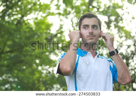 portrait of sporty male runner adjusting his earphone during jogging with copy space - stock photo