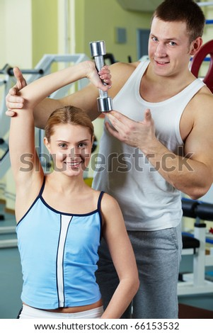 Portrait of sporty woman doing exercise with dumbbell and her trainer near by - stock photo