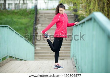 Portrait of sporty woman doing stretching workout in park before jogging. Female athlete runner getting ready for running routine on the bridge. Sport active lifestyle concept. Full length - stock photo