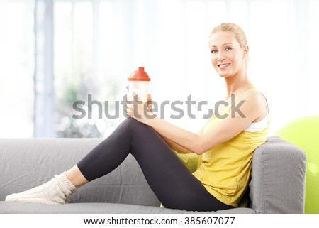 Portrait of sporty woman holding in her hand protein shaker while sitting at home after workout. - stock photo