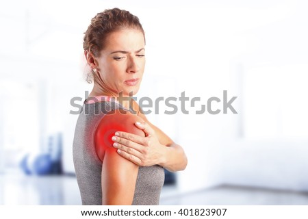 Portrait of sporty woman putting her hand on red spots on while has sport injury in her shoulder. - stock photo
